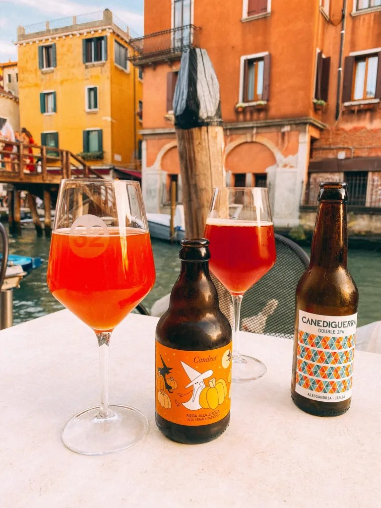 Along a canal in venice, craft beer bottles and glasses of beer with colorful buildings on the other side of the canal in Italy.