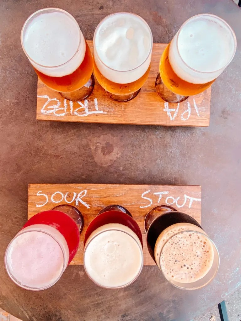 picture of two beer flights with three beers each on wooden boards with chalk writing indicating what kind of beers they are on a table top.