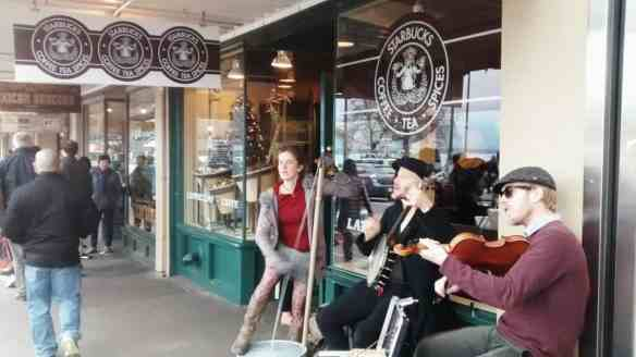 Musicians perform out the front of the original Starbucks in Seattle.