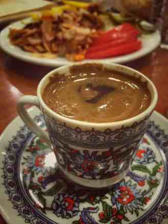 A cup of turkish coffee in Istanbul with food in the background
