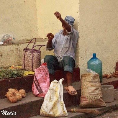 A man sells his produce in downtown Stone Town