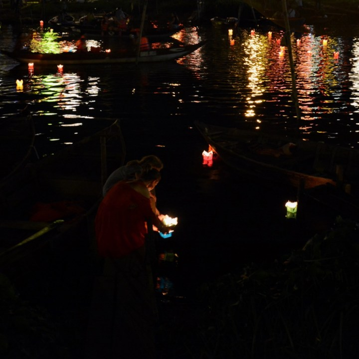 hoi an by night with kids swimming candle