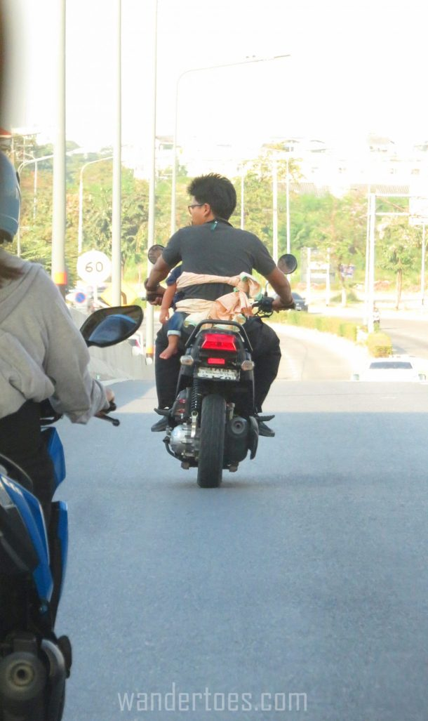 Thailand Traffic crazy scary things we see baby strapped to adult with a sheet on a motorbike