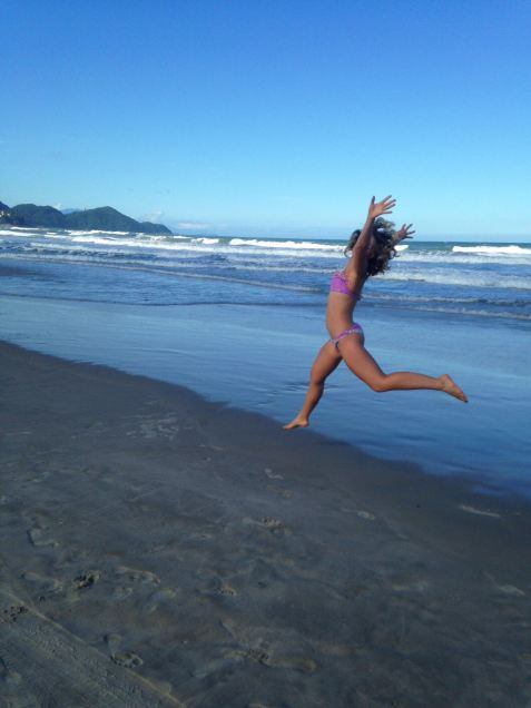 a girl caught mid jump on a beach in Brazil.