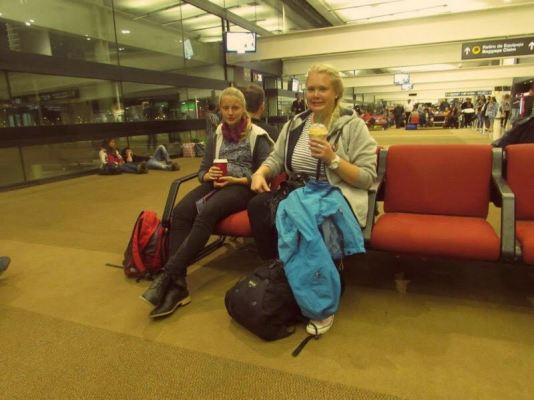 two blonde women waiting for a flight.