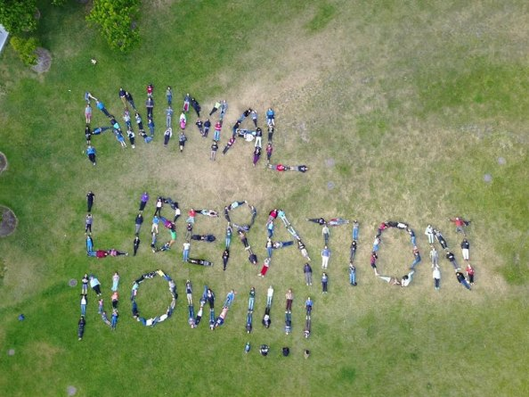 "photo taken from above, human bodies spell out the words ""animal liberation now!!!"""