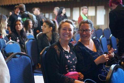 Two woman sitting, ready to listen and learn in a conference setting.