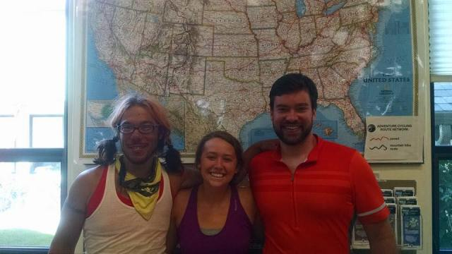 three people standing in front of a. map of the US inside an Adventure Cycling office.