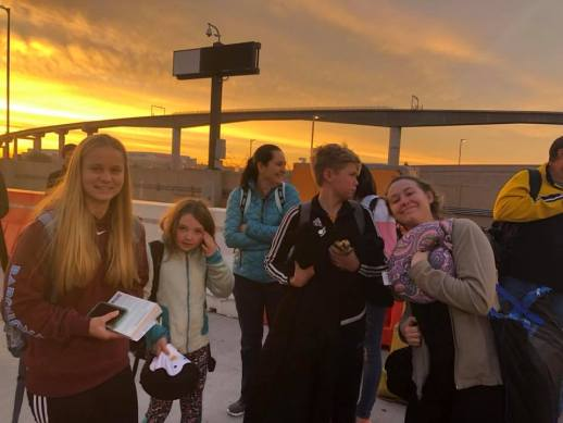 a family standing outside the airport with the sunrise behind them