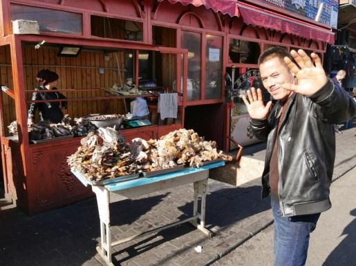 Uighur market: sheep head and a waving vendor.// Uigurischer Markt: Schafskopf und ein winkender Verkäufer.