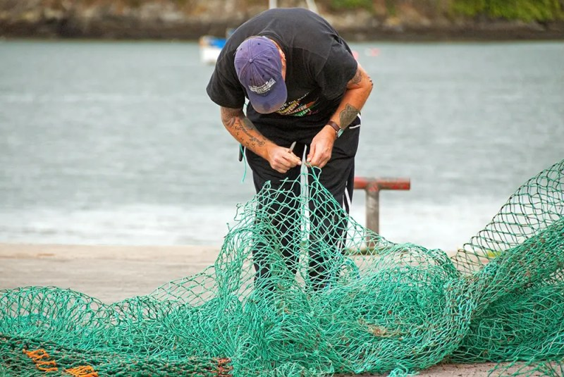 Fisherman mending his net