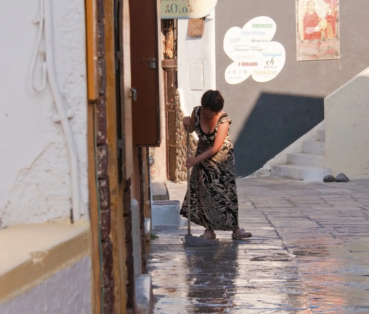 Woman cleaning walkway in front of shop, Oia, Santorini, Greece