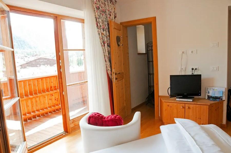 Bed, chair, door to balcony and door to walk in closet