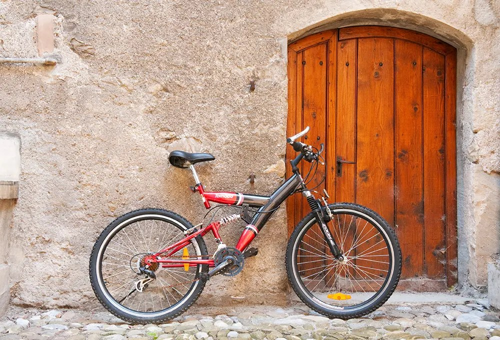 Bike next to wooden door along the Terrasses de Lavaux trail