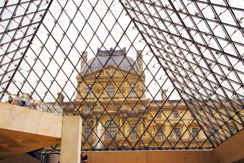 Looking out the glass pyramid of the Lourve lobby to the buildings of the Palais du Louvre, Paris, France