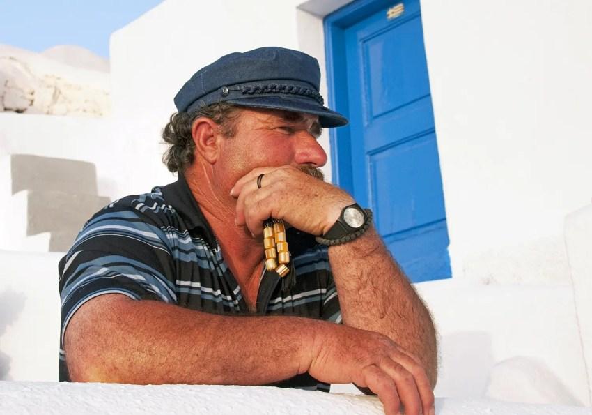 Greek man with prayer beads looking out to Aegean Sea, Oia, Santorini, Greece
