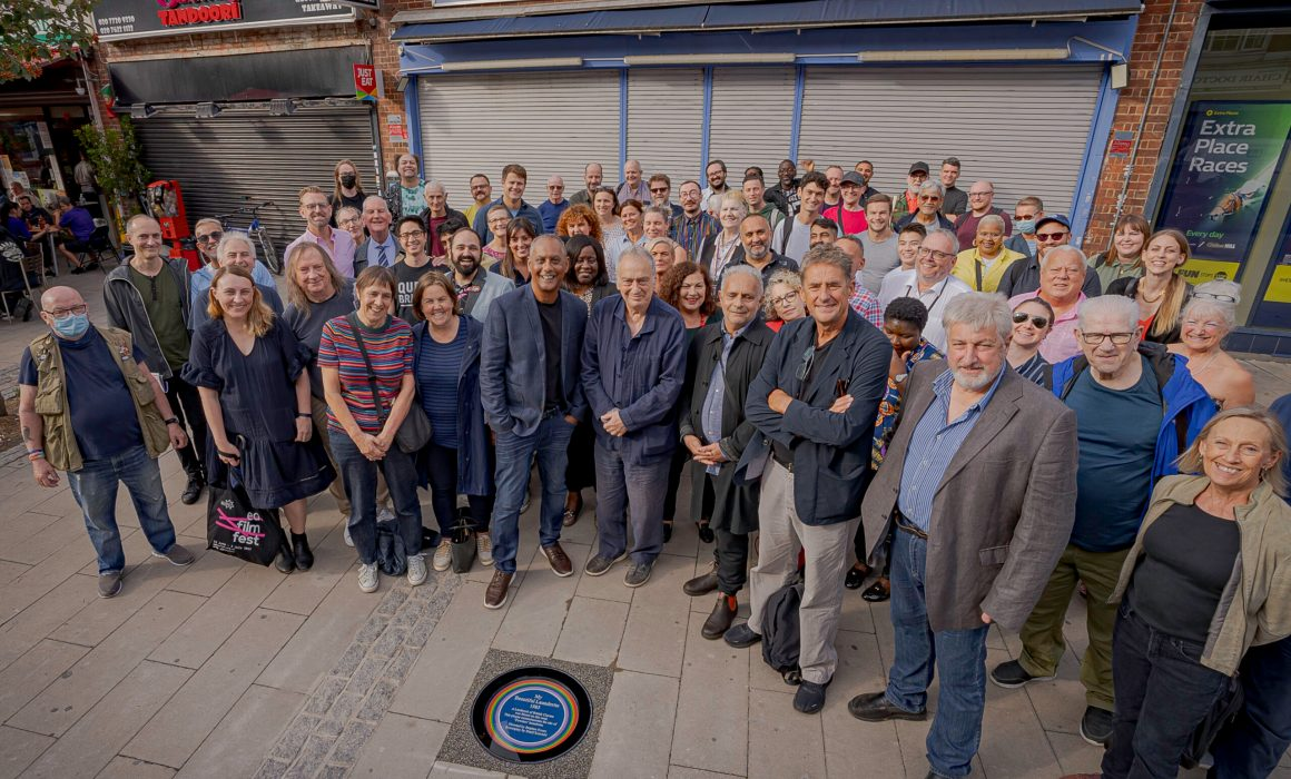 The crowd at the My Beautiful Launderette Unveiling, with the plaque in the foreground