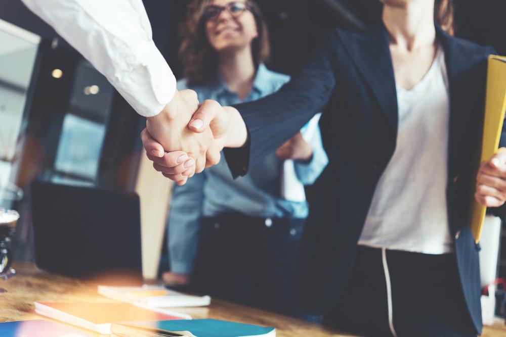 握手し合うビジネスマンとビジネス服の女性