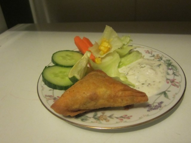 One Samosa on my plate with salad and a serving of yogurt