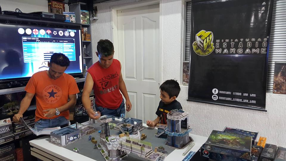 La familia de Miniaturas Estadio Wargame jugando Infinity