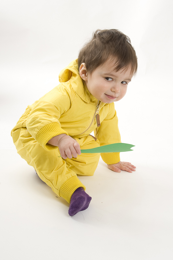 Fashion photograph of a toddler boy wearing a yellow jumpsuit by Anna Hindocha/Warm Glow Photo