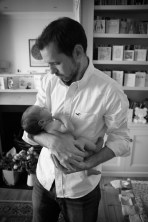 Black and white photograph of a father holding his newborn baby girl by Anna Hindocha/Warm Glow Photo