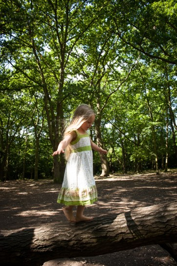 Young girl balancing on a tree in Streatham Common Woods, photographed by Anna Hindocha/Warm Glow Photo
