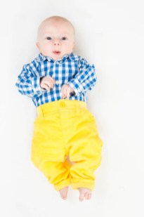 Studio photograph of young baby boy in bright clothes. Photographed by Anna Hindocha/Warm Glow Photo
