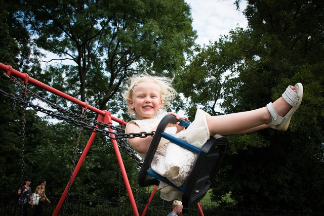 Young girl in party dress on swing in Belair Park, Dulwich. Photographed by Anna Hindocha/Warm Glow Photo