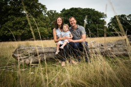 Toddler girl and her parents in Bushy Park, Teddington in autumn photographed by Anna Hindocha/Warm Glow Photo