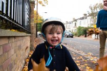 Young boy playing in autumn leaves on location family lifestyle shoot. Photographed by Anna Hindocha/Warm Glow Photo