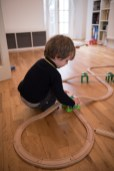 Young boy playing with train tracks on location family lifestyle shoot. Photographed by Anna Hindocha/Warm Glow Photo