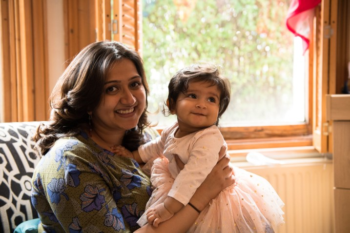 7 month old baby girl with her mother in front of window.