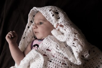 Newborn baby wrapped in handmade shawl, lit with window light.