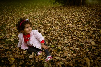 Young girl sitting in autumn leaves in Battersea Park.