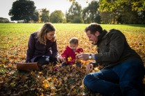 Parents and toddler girl sat in autumn leaves in Brockwell Park. Photographed by Anna Hindocha/Warm Glow Photo