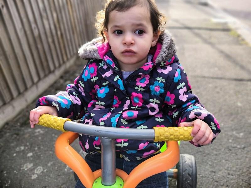 Girl riding trike.