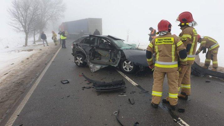 na środku drogi rozbity samochód osobowy przy nim służby ratownicze, w tle samochód ciężarowy