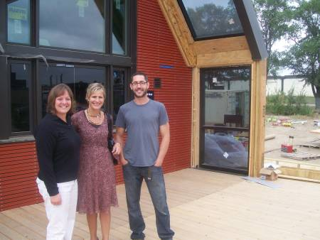Mary Stage (Web administrator) and Carla Warner (director of sales) pose with Dan Handeen outside the U of M's Icon Solar House.