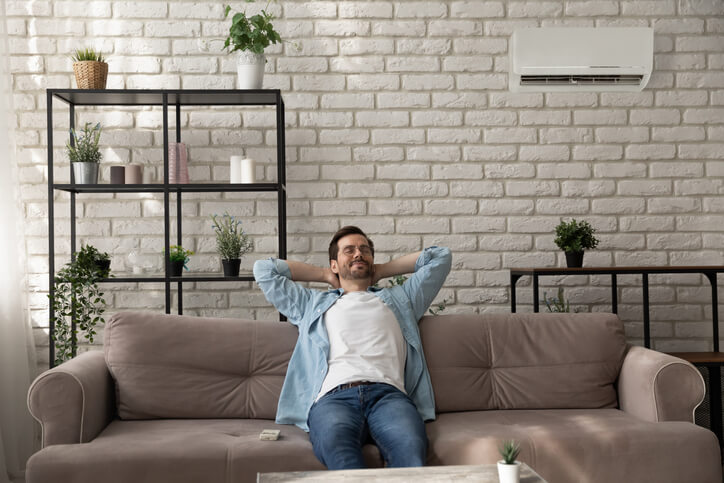 Man relaxing in room with ductless AC.