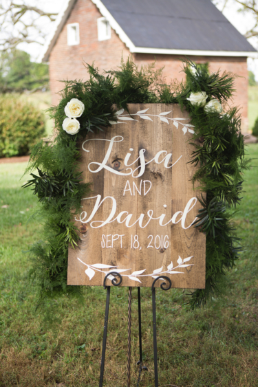 Kentucky summer estate wedding- Outdoor wedding ceremony with all white flowers and greenery around rustic wedding sign