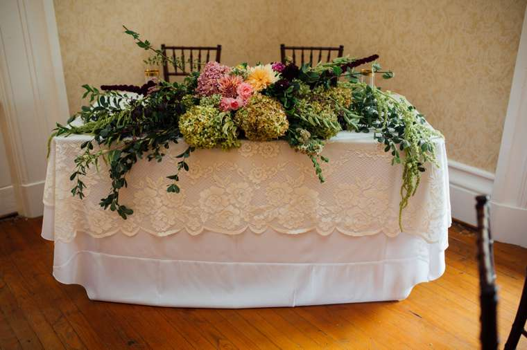Sweetheart table with ivory lace overlay and large floral swag