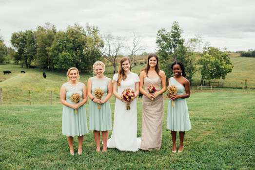 Bridal party in green pasture with fall floral bouqets