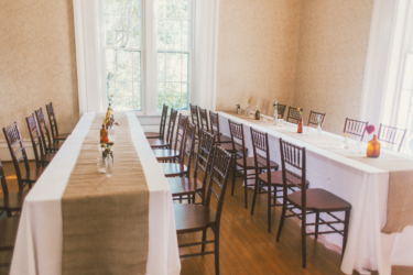 Banquet style tables with burlap runners and budvases