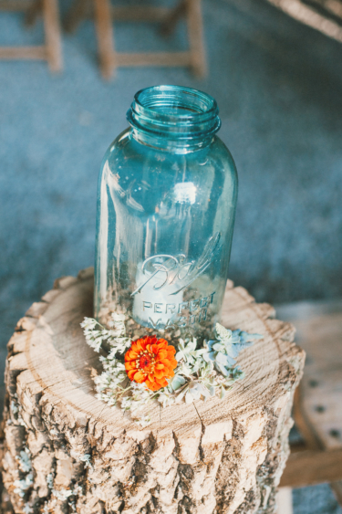 Aisle markers at barn ceremony with flowers and mason jar