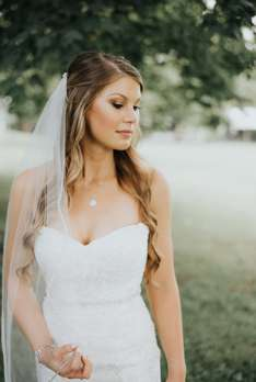 Bride dressed in a sweetheart cut mermaid dress with soft airy veil