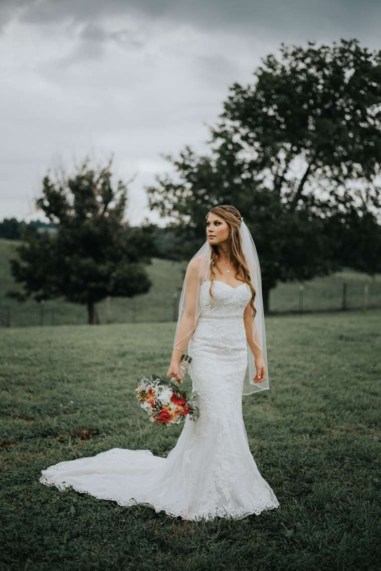 Country Rustic Bride in mermaid dress with train during farm wedding in central Kentucky