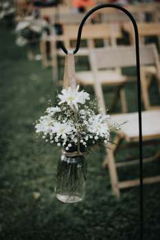 Daisies and baby's breath in mason jar on shepard's hooks for aisle at rustic country outdoor wedding