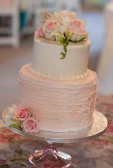 Pale pink and ivory two-tier wedding cake with spray roses