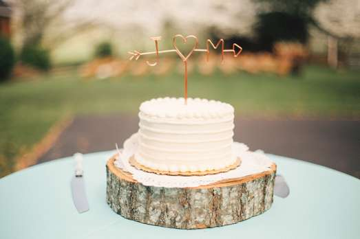 Single-tier textured wedding cake on wood slice with copper wire cake topper
